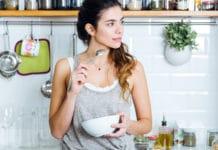 Piękna młoda kobieta jedząca śniadanie w kuchni