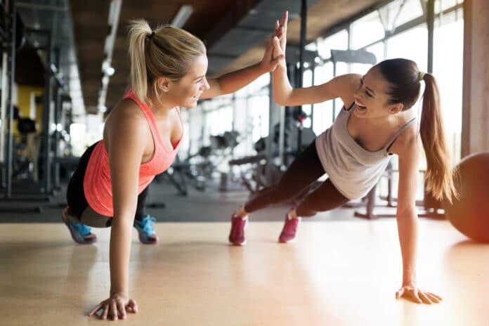 Dwie młode uśmiechnięte kobiety ćwiczące na siłowni.